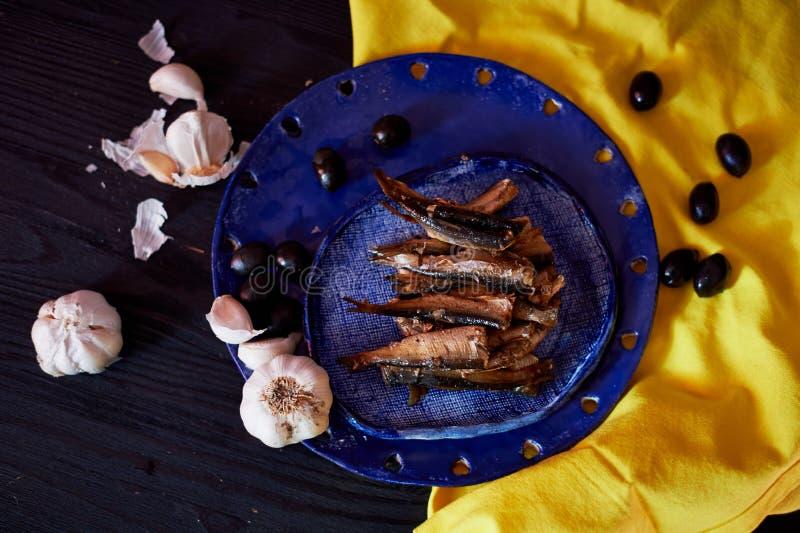 Κίτρινο μπλε γάμμα αντίθεσης Κλυπέα στο μπλε πιάτο στην κίτρινη πετσέτα Πλαισιωμένος με το σκόρδο και τις ελιές στοκ εικόνα