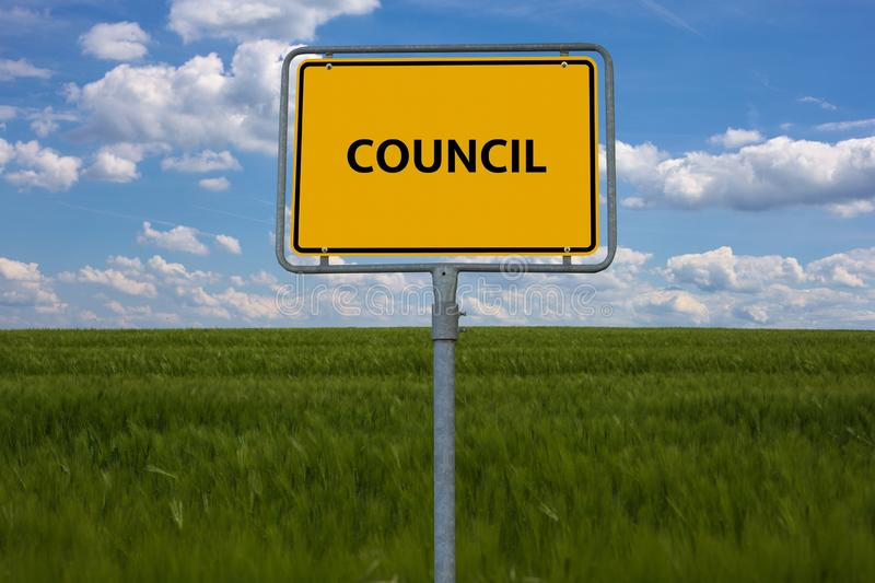 Κίτρινο οδικό σημάδι το Συμβούλιο λέξης επιδεικνύεται Το σημάδι στέκεται σε έναν τομέα με το μπλε υπόβαθρο στοκ εικόνες με δικαίωμα ελεύθερης χρήσης