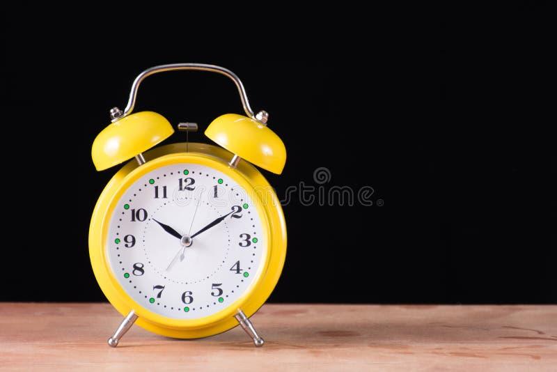 Κίτρινο παλαιό αναδρομικό ρολόι στο ξύλινο γραφείο και το μαύρο υπόβαθρο στοκ φωτογραφίες