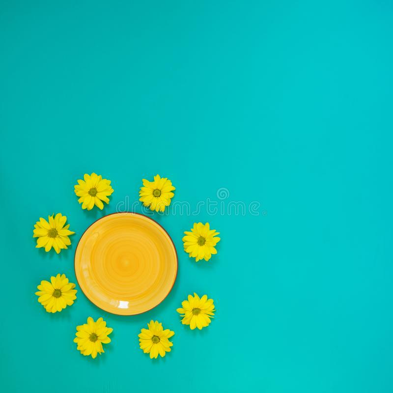 Κίτρινο πιάτο που περιβάλλεται από τα κίτρινα λουλούδια χρυσάνθεμων στοκ εικόνα