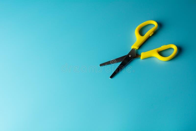 Κίτρινο πλαστικό ψαλίδι σε μπλε χαρτί. - φόντο στοκ εικόνες με δικαίωμα ελεύθερης χρήσης