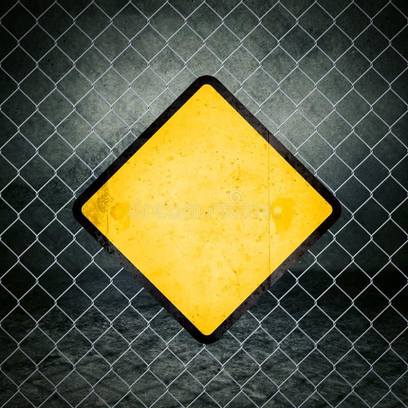 Κίτρινο προειδοποιητικό σημάδι Grunge στο φράκτη Chainlink των βιομηχανικών εμπορευμάτων στοκ εικόνες