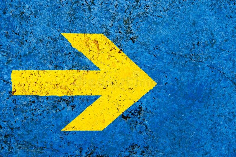Κίτρινο σημάδι κατεύθυνσης βελών πέρα από το ζωηρό φωτεινό μπλε τοίχο πετρών χρώματος με τις ατέλειες και τις ρωγμές στοκ φωτογραφίες με δικαίωμα ελεύθερης χρήσης