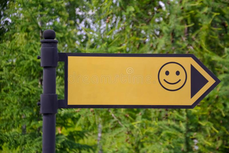 Κίτρινο σημάδι με ένα χαμόγελο στην οδό Το βέλος παρουσιάζει πρότυπο στοκ εικόνες