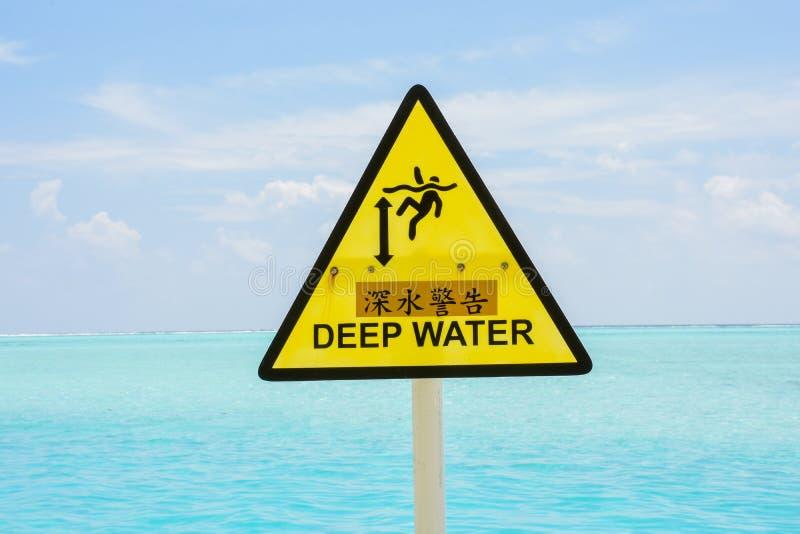 Κίτρινο σημάδι προσοχής βαθιά νερών στον ωκεανό στοκ εικόνα
