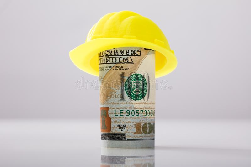 Κίτρινο σκληρό καπέλο πέρα από το κυλημένο επάνω αμερικανικό τραπεζογραμμάτιο στοκ φωτογραφίες με δικαίωμα ελεύθερης χρήσης