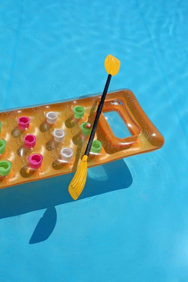 Κίτρινο στρώμα αέρα με το κουπί στην πισίνα στοκ φωτογραφία