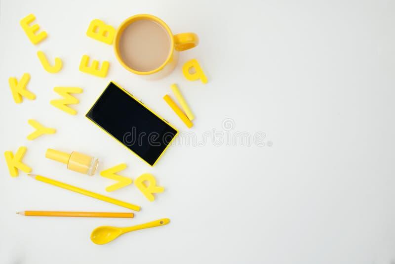 Κίτρινο φλυτζάνι, κίτρινο τηλέφωνο, επιστολές και μολύβια στο άσπρο υπόβαθρο τοποθετήστε το κείμενο επάνω από την όψη στοκ εικόνα με δικαίωμα ελεύθερης χρήσης