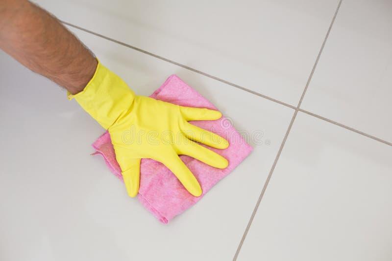 Κίτρινο φορημένο γάντια χέρι με τον καθαρισμό του κουρελιού που σκουπίζει το πάτωμα στοκ φωτογραφία