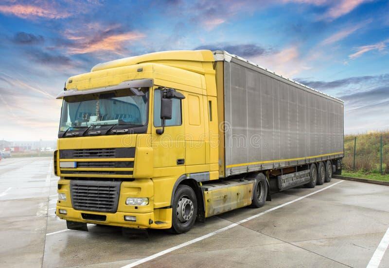 Κίτρινο φορτηγό στο δρόμο Μεταφορά φορτίου στοκ φωτογραφία