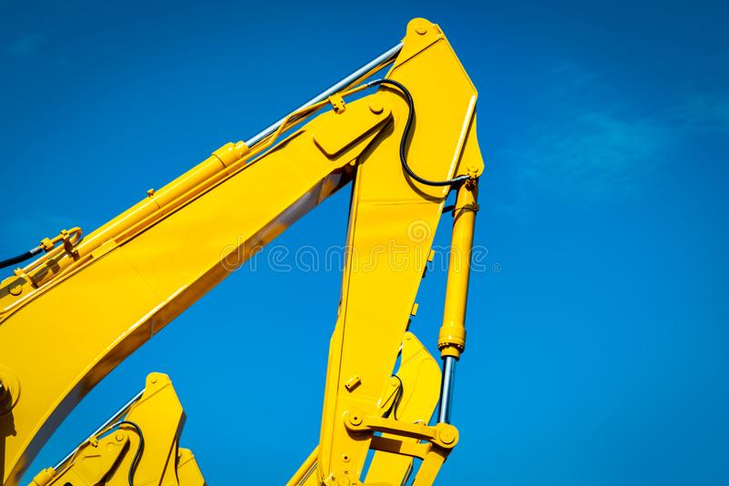 Κίτρινο backhoe με τον υδραυλικό βραχίονα εμβόλων ενάντια στο σαφή μπλε ουρανό Βαριά μηχανή για την ανασκαφή στο εργοτάξιο οικοδο στοκ φωτογραφίες