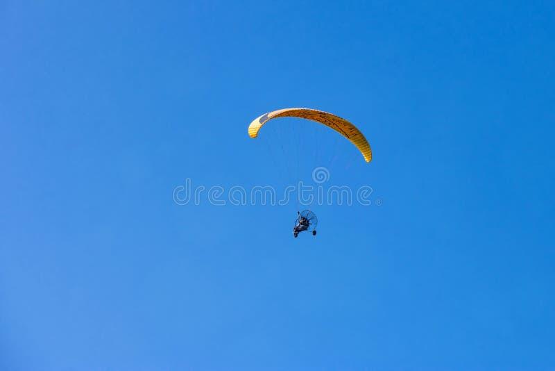 Κίτρινο moto-ανεμόπτερο που πετά πέρα από το σαφή μπλε ουρανό στοκ εικόνα