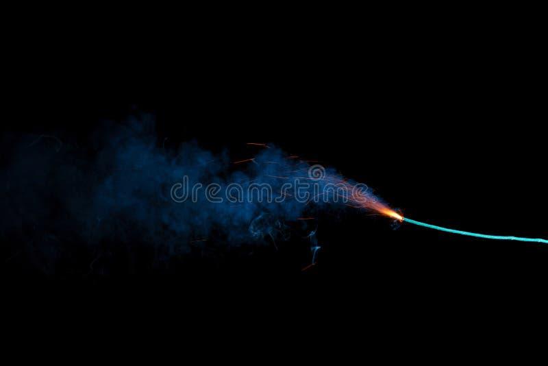 Καίγοντας θρυαλλίδα με τους πορτοκαλιούς σπινθήρες και τον μπλε καπνό στοκ φωτογραφίες