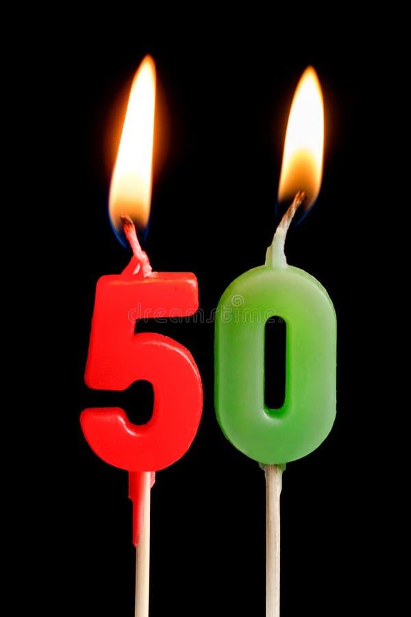 Καίγοντας κερί υπό μορφή πέντε αριθμών αριθμών, ημερομηνίες για το κέικ στο μαύρο υπόβαθρο Η έννοια του εορτασμού ενός βισμουθίου στοκ φωτογραφίες