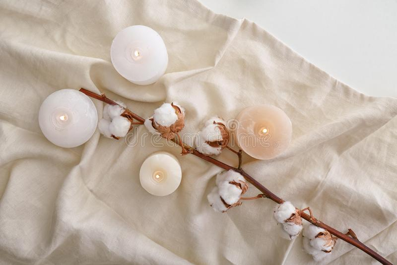 Καίγοντας κεριά και λουλούδια βαμβακιού στο μαλακό ύφασμα, τοπ άποψη στοκ φωτογραφία με δικαίωμα ελεύθερης χρήσης
