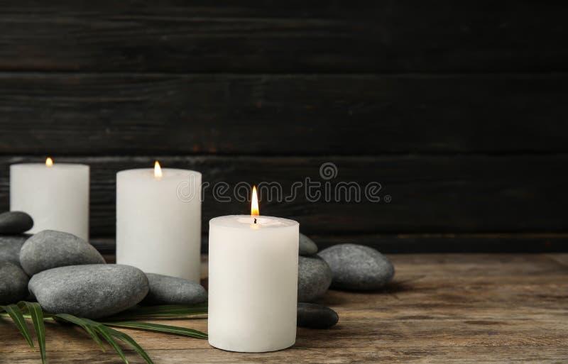 Καίγοντας κεριά, πέτρες SPA και φύλλο φοινικών στον ξύλινο πίνακα στοκ εικόνες με δικαίωμα ελεύθερης χρήσης