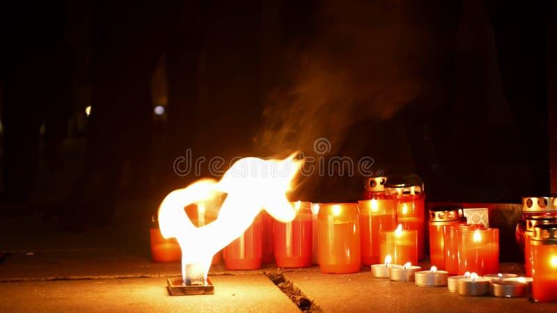 Καίγοντας κεριά ως μνημείο στο θάνατο ενός ατόμου, φλόγες του φλογερού κοκκίνου πυρκαγιάς, μια θέση στο τετράγωνο, ένας μαγικός στοκ φωτογραφίες