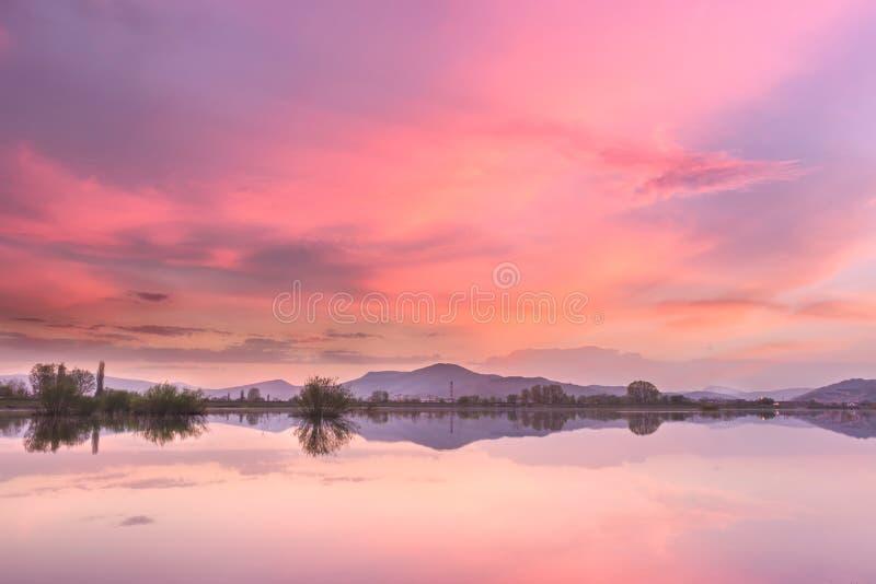 Καίγοντας ουρανός ηλιοβασιλέματος πέρα από την τεχνητή αντανακλαστική λίμνη στοκ εικόνα