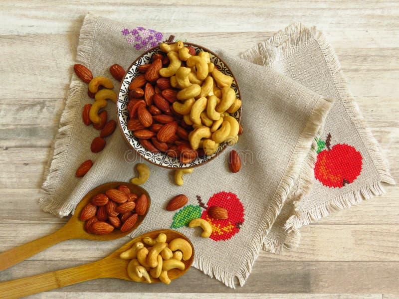 Καβουρντισμένα Φυσικά αμύγδαλα Καρύδια Badam και Cashew σε πορσελάνη Δύο ξύλινα κουτάλια και Nuts χυμένα πάνω σε χειροποίητο πανί στοκ φωτογραφία με δικαίωμα ελεύθερης χρήσης