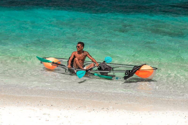 Καγιάκ γυαλιού με ένα τοπικό άτομο που κολυμπά την τυρκουάζ θάλασσα σε Bora Bora, Ταϊτή - τον Ιανουάριο του 2018 στοκ φωτογραφία