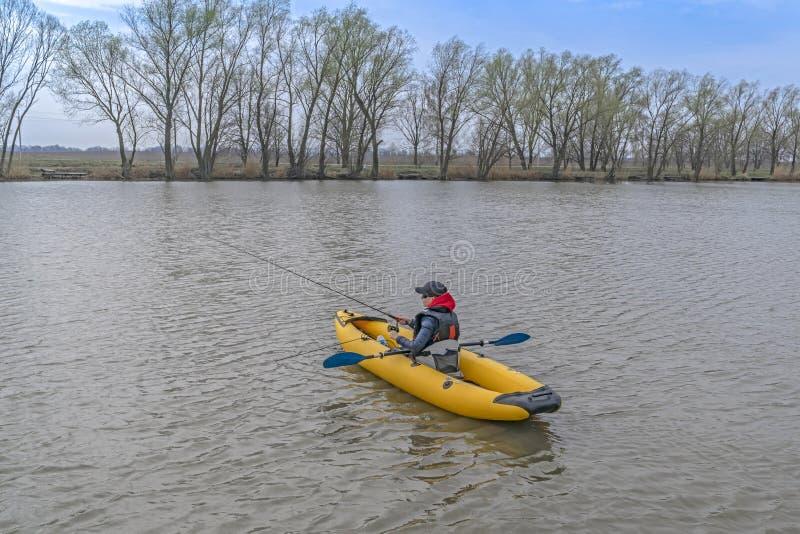Καγιάκ που αλιεύει στη λίμνη Fisherwoman στη inflateble βάρκα με το fishi στοκ εικόνες