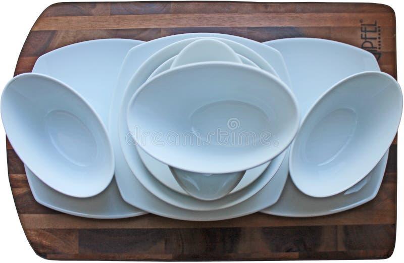 Καθαρά άσπρα πιάτα στον καφετή ξύλινο πίνακα στοκ εικόνα