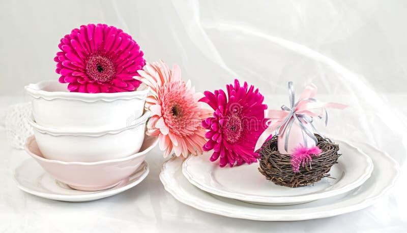Καθαρά πιάτα και φλυτζάνια στο υπόβαθρο κρητιδογραφιών με τα ρόδινα λουλούδια και το αυγό Πάσχας στοκ εικόνες