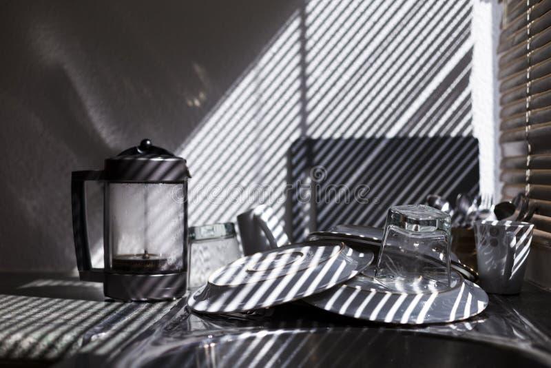 καθαρά πιάτα στην κουζίνα Όμορφο φως από το παράθυρο τυφλό : στοκ εικόνες