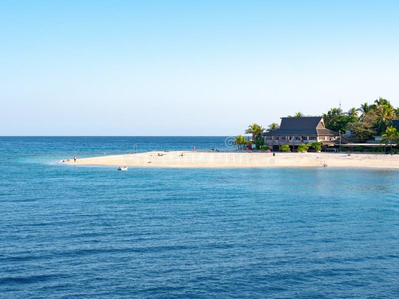 Καθαρή άσπρη άμμος μπροστά από ένα θέρετρο σε ένα τροπικό νησί στοκ εικόνα με δικαίωμα ελεύθερης χρήσης