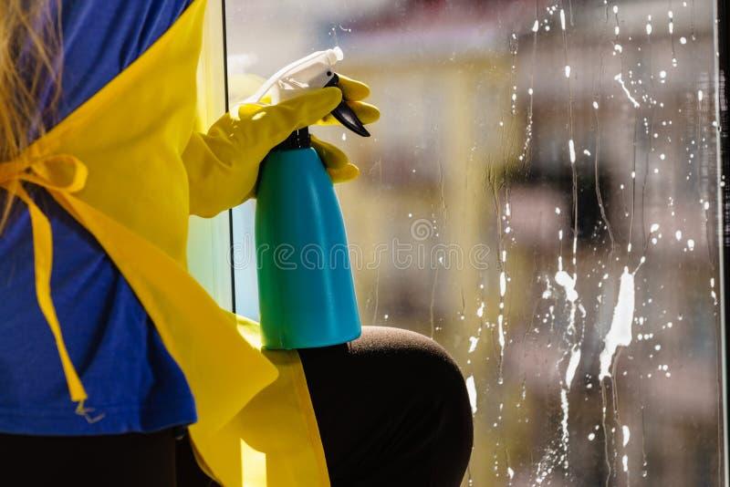 Καθαρίζοντας απορρυπαντικό παραθύρων προσώπων ψεκάζοντας στοκ φωτογραφία