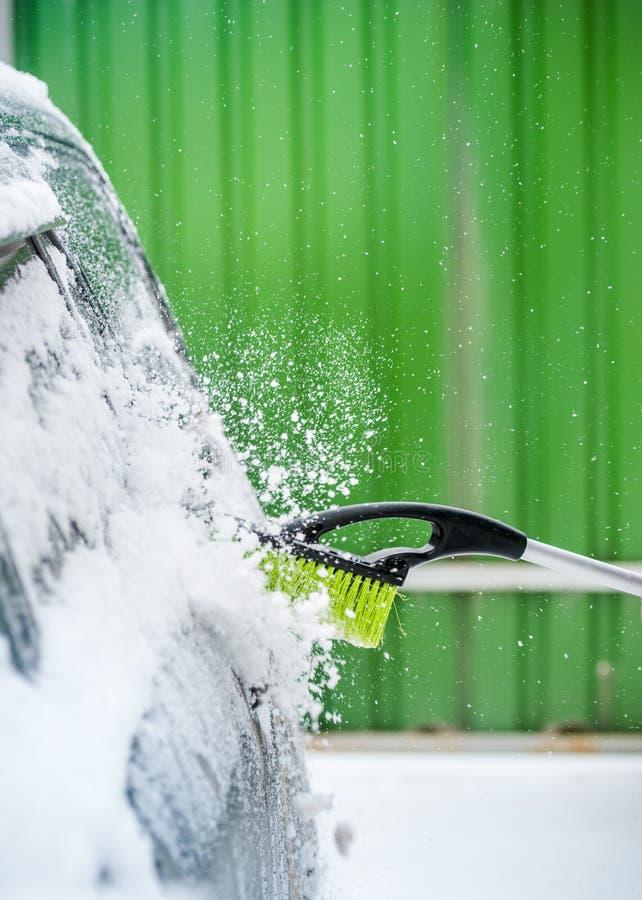 Καθαρίζοντας αυτοκίνητο ατόμων από το χιόνι στοκ εικόνες