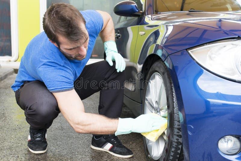 Καθαρίζοντας αυτοκίνητο ατόμων με το σπογγιστή στοκ φωτογραφία με δικαίωμα ελεύθερης χρήσης