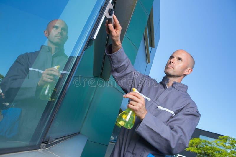 Καθαρίζοντας γυαλί χεριών υπαλλήλων στοκ φωτογραφία με δικαίωμα ελεύθερης χρήσης