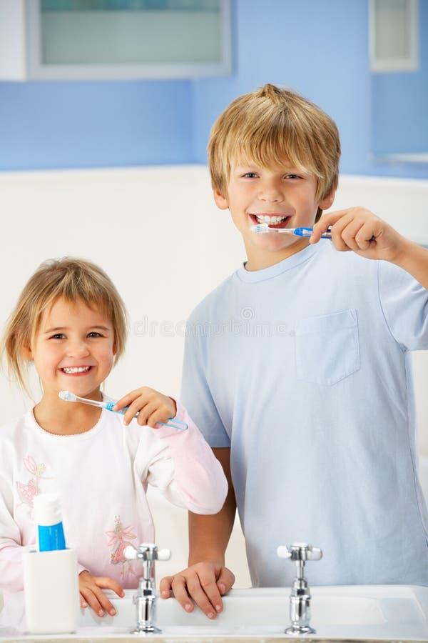 καθαρίζοντας δόντια κοριτσιών αγοριών λουτρών στοκ φωτογραφίες