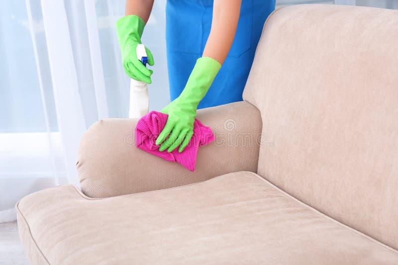 Καθαρίζοντας καναπές γυναικών με το ξεσκονόπανο στοκ εικόνα με δικαίωμα ελεύθερης χρήσης
