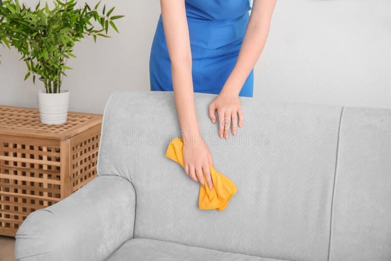 Καθαρίζοντας καναπές γυναικών με το ξεσκονόπανο στοκ φωτογραφία
