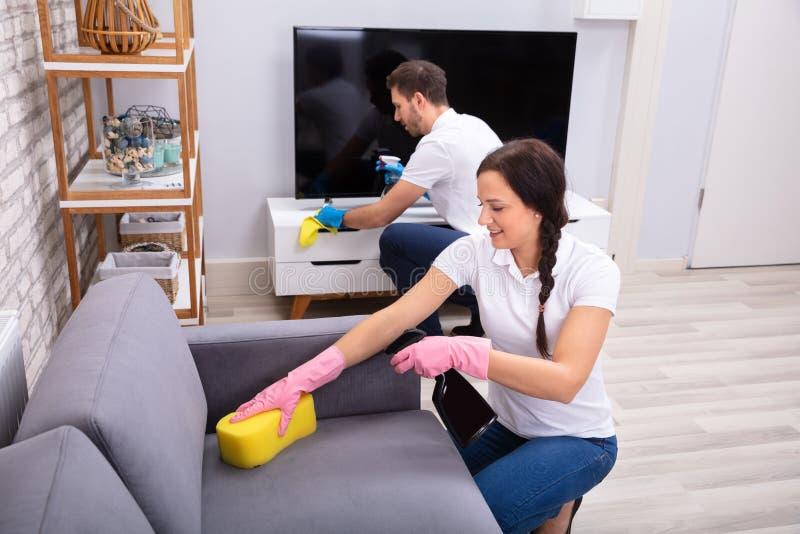 Καθαρίζοντας καναπές και τηλεόραση στοκ εικόνες