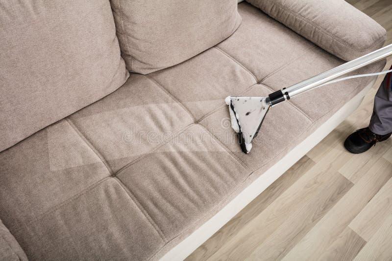 Καθαρίζοντας καναπές προσώπων με την ηλεκτρική σκούπα στοκ φωτογραφία με δικαίωμα ελεύθερης χρήσης