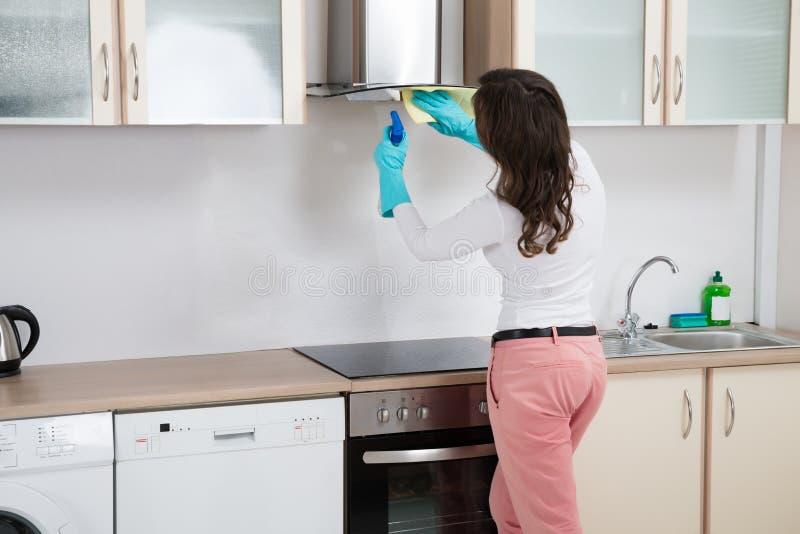Καθαρίζοντας κουκούλα κουζινών γυναικών με το κουρέλι στοκ εικόνα με δικαίωμα ελεύθερης χρήσης