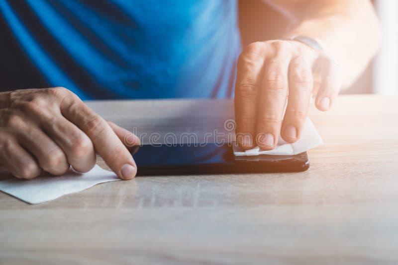 Καθαρίζοντας οθόνη smartphone ατόμων με το ύφασμα στοκ εικόνα