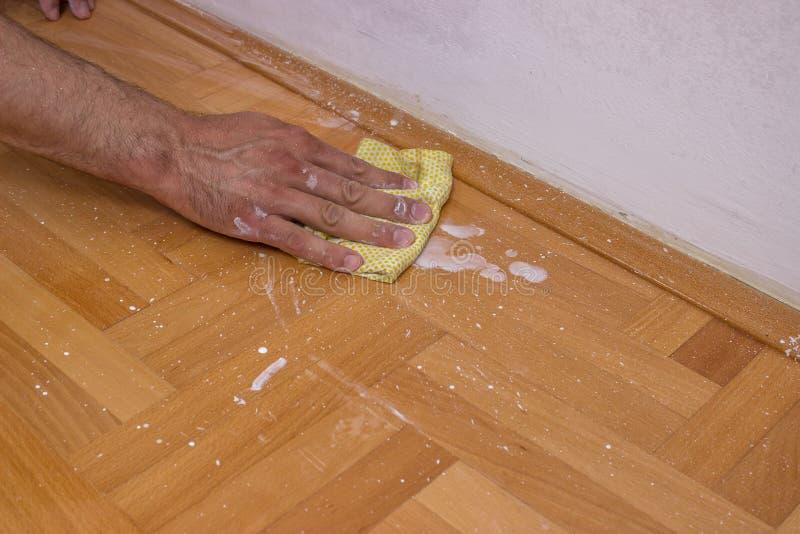 Καθαρίζοντας πάτωμα ατόμων μετά από να χρωματίσει τον τοίχο στοκ φωτογραφίες