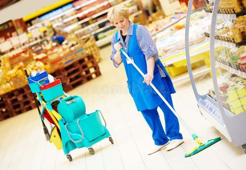 Καθαρίζοντας πάτωμα εργαζομένων με τη σφουγγαρίστρα στοκ εικόνα