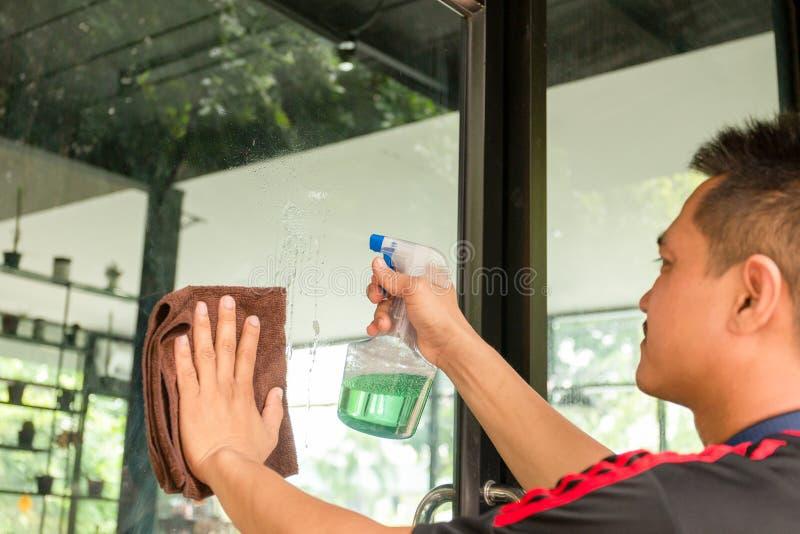 Καθαρίζοντας παράθυρα εργαζομένων ατόμων με το μπουκάλι υφασμάτων και ψεκασμού στη καφετερία στοκ φωτογραφίες με δικαίωμα ελεύθερης χρήσης