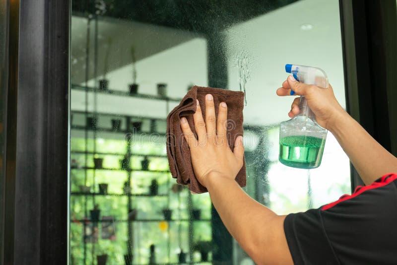 Καθαρίζοντας παράθυρα εργαζομένων ατόμων με το μπουκάλι υφασμάτων και ψεκασμού στη καφετερία στοκ φωτογραφία με δικαίωμα ελεύθερης χρήσης