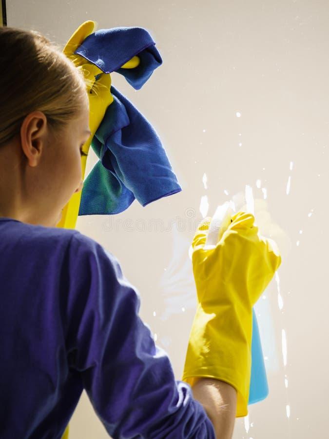 Καθαρίζοντας παράθυρο γυναικών στο σπίτι στοκ εικόνες