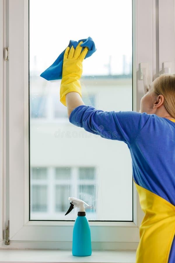 Καθαρίζοντας παράθυρο κοριτσιών που χρησιμοποιεί στο σπίτι το καθαριστικό κουρέλι στοκ εικόνα με δικαίωμα ελεύθερης χρήσης