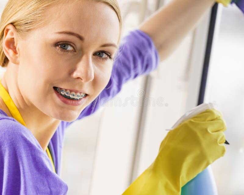 Καθαρίζοντας παράθυρο κοριτσιών στο σπίτι στοκ φωτογραφία με δικαίωμα ελεύθερης χρήσης