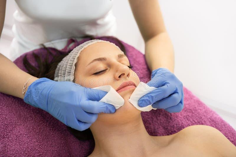 Καθαρίζοντας πελάτης Cosmetologist του θηλυκού προσώπου με το μαξιλάρι βαμβακιού στοκ εικόνες