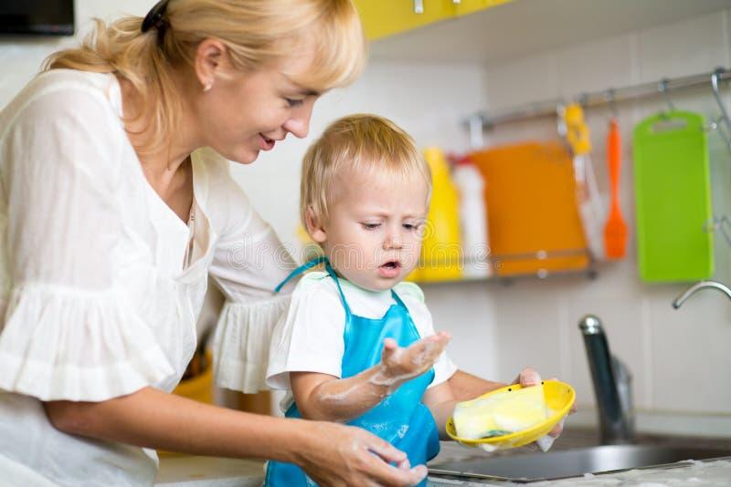 Καθαρίζοντας πιάτα μητέρων και γιων από κοινού στοκ εικόνες με δικαίωμα ελεύθερης χρήσης