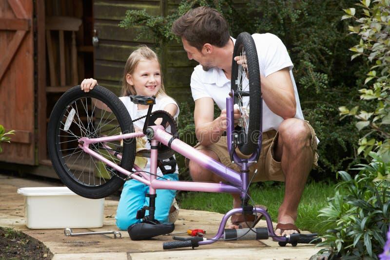 Καθαρίζοντας ποδήλατο πατέρων και κορών από κοινού στοκ εικόνες με δικαίωμα ελεύθερης χρήσης